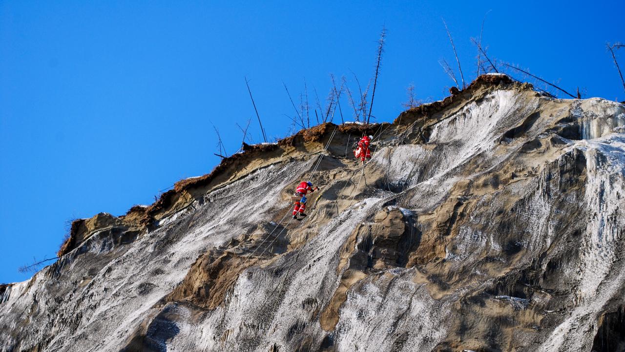 duas pessoas escalando os penhascos da cratera Batagaika